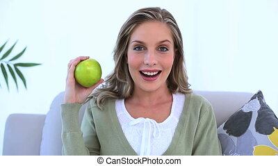 Blond woman holding a green apple