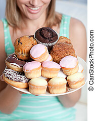 Blond woman holding a plate of cakes