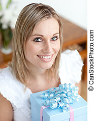 Blond woman holding a present
