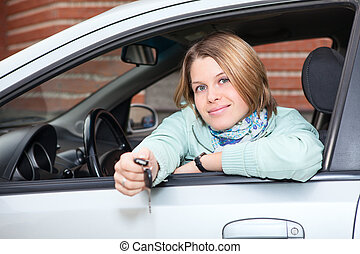 Blond woman holding car key in hands