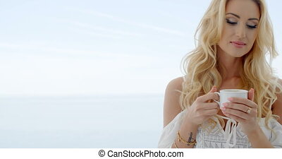 Blond Woman Holding Coffee Cup in front of Ocean