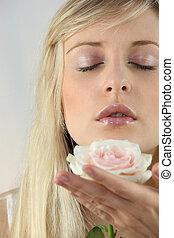 Blond woman holding flower
