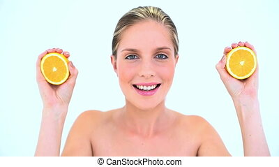 Blond woman holding two slices of orange against a white...