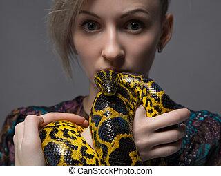 Blond woman holding yellow anaconda