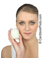 Blond woman holding yogurt