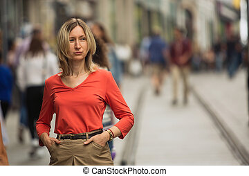 Blond woman in a red blouse standing on the street.