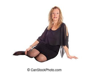 Blond woman in black dress sitting on floor.