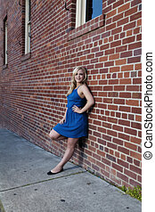 Blond Woman In Blue Dress Leaning On Brick Wall