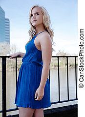 Blond Woman In Blue Dress Standing Outdoors