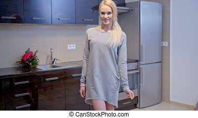 Blond Woman in Gray Dress Standing at the Kitchen