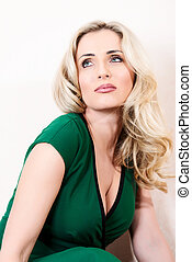 Blond woman in green dress posing on white vertical
