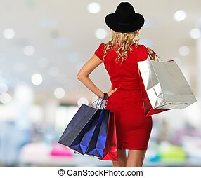 Blond woman in hat and red dress with shopping bags in shop interior