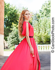 Blond woman in long red dress outdoors
