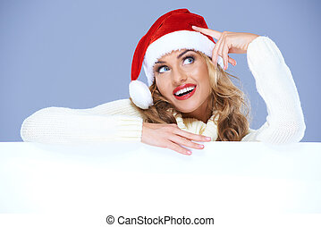 Blond woman in Santa Hat resting on white board