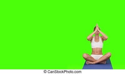 Blond woman in sportswear doing yoga