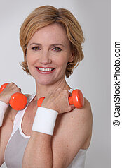 Blond woman in sportswear holding weights