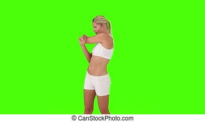 Blond woman in sportswear stretching herself