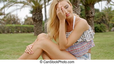 Blond Woman in Summer Clothes Sitting on Grass