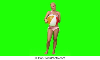 Blond woman in swimsuit playing with a ball