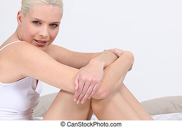 Blond woman in underwear sat on bed