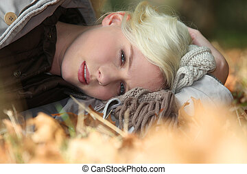 Blond woman laying in leaves