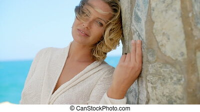 Blond Woman Leaning Against Ocean Front Stone Wall