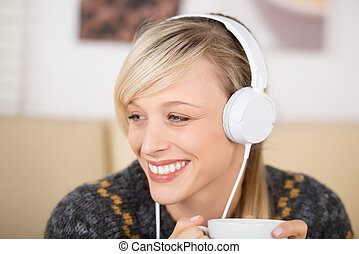 Blond woman listening music and drinking coffee