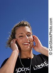 Blond woman listening to music in the sun