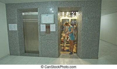 Blond Woman Little Girl Get off Elevator to Corridor