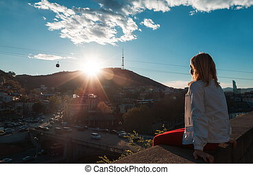 blond woman looking at the city at sunset