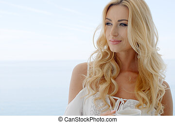 Blond Woman Looking to the Side in front of Ocean