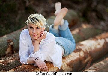 Blond Woman Lying On Logs