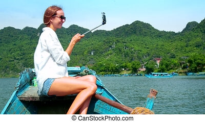 blond woman makes selfie sailing on boat past hilly bank