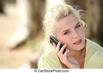Blond woman making call outdoors
