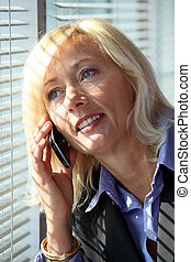 Blond woman making phone call by window blinds