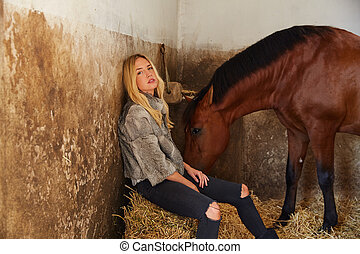 Blond woman on an indoor stable with horse