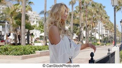 Blond Woman on Palm Tree Lined Promenade