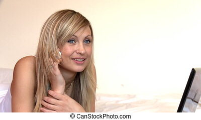 Blond woman on phone lying on bed