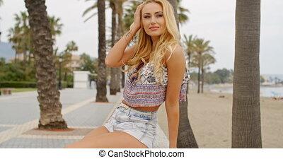 Blond Woman on Stone Wall on Beach Promenade - Waist Up...