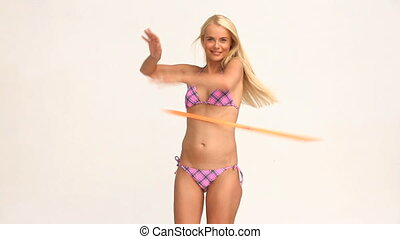 Blond woman playing with a hoop