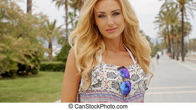 Blond Woman Playing with Strand of Hair Outdoors - Smiling...