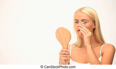 Blond woman plucking her eyelashs