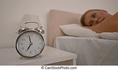 Blond woman pushing the alarm clock in bed