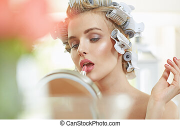 Blond woman putting on a lipstick