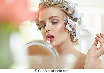 Blond woman putting on a lipstick