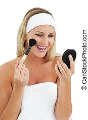 Blond woman putting on make-up