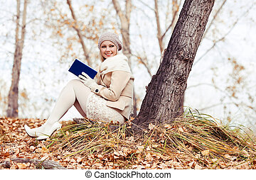 blond woman reading in the park