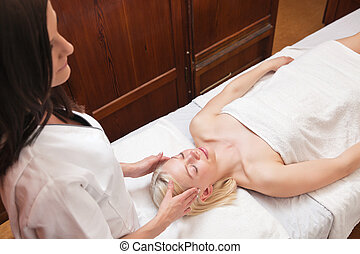 Blond woman receiving head massage