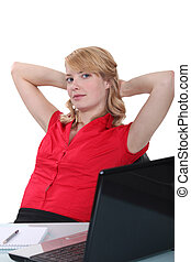 Blond woman relaxing at desk