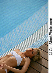 Blond woman resting next to swimming pool